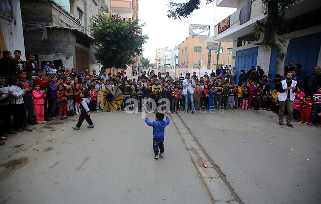 Volunteers of the Friday of Joy Initiative, play with Palestinian children in the street in al-Shati refugee camp, in Gaza city, February 6, 2015. Ten Palestinian volunteers organise street games, painting and drama, every Friday afternoon in the streets of  refugee camps and provide outlets for the children's energy with organised games, dancing and singing, which gives extra psycho-social support to vulnerable children. Photo by Khaled al-Sabbah