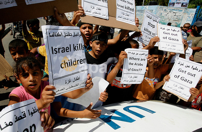 Palestinian children hold posters and banners outside an UNRWA school during a protest against the killing of children on August 11, 2014 in Rafah in the southern Gaza City, during a 72-hour ceasefire observed in the Gaza Strip. Almost 12 hours into the truce, the skies over Gaza remained calm, with no reports of violations on any side and signs of life emerging on the streets of the war-torn coastal enclave which is home to 1.8 million Palestinians. Photo by Abed Rahim Khatib