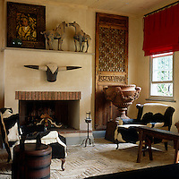 Alongside cow-hide armchairs this living room is filled with an eclectic collection including Chinese ceramic horses on the mantelpiece and a large classical urn