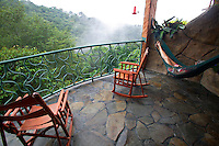A visitor (mr) relaxes and enjoys the view from the balcony of a room at the La Paz Waterfall Gardens and Peace Lodge, Costa Rica