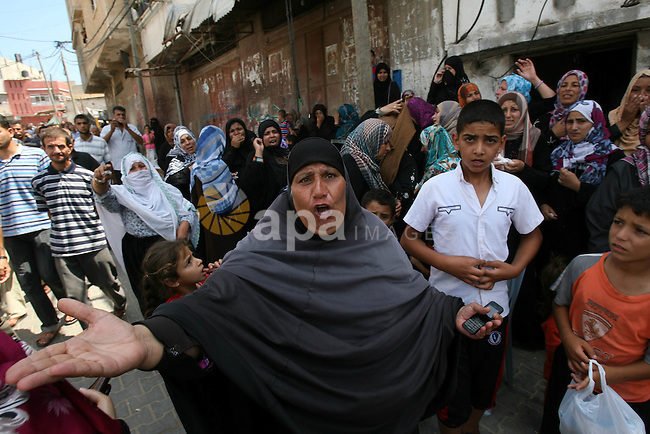 Relatives of Palestinians from the al-Najar family, who medics said were killed by an Israeli air strike on their house, mourn during their funeral in Khan Younis in the southern Gaza Strip July 26, 2014. The Gaza Health Ministry said 18 members of a single family were killed by Israeli tank shelling in the southern Gaza Strip shortly before the truce took effect at 8 a.m. (6 a.m. British Time). An Israeli military spokeswoman said she was checking the report. A 12-hour humanitarian truce went into effect on Saturday after Israel and Palestinian militant groups in the Gaza Strip agreed to a U.N. request for a pause in fighting and efforts proceeded to secure a long-term ceasefire moved ahead. Photo by Eyad Al Baba