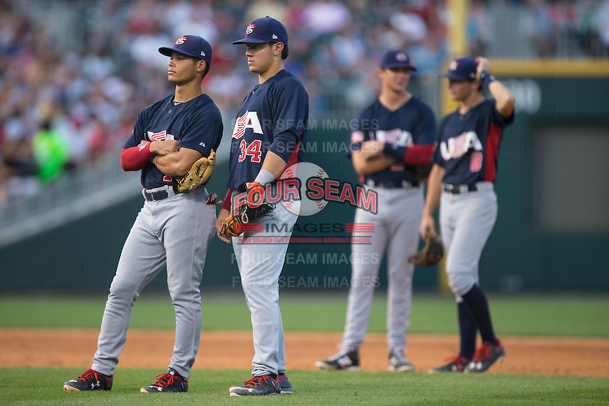 (L-R) US Collegiate National Team infielders Bryson Brigman (7), KJ Harrison (34), Bobby Dalbec (24) and Ryan Howard (8) wait for the relief pitcher to complete his warm up tosses during the game against the Cuban National Team at BB&T BallPark on July 4, 2015 in Charlotte, North Carolina.  The United State Collegiate National Team defeated the Cuban National Team 11-1.  (Brian Westerholt/Four Seam Images)