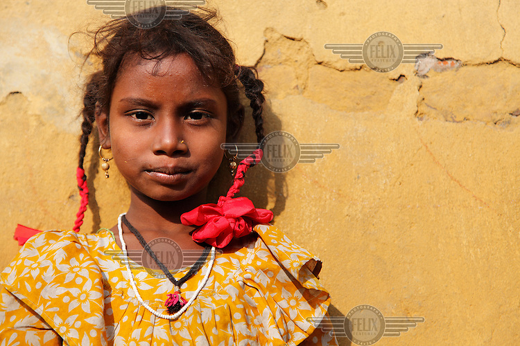 Young girl with red ribbons in her hair.