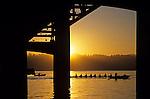 Sunrise on Lake Washington below bridge with eight woman crew