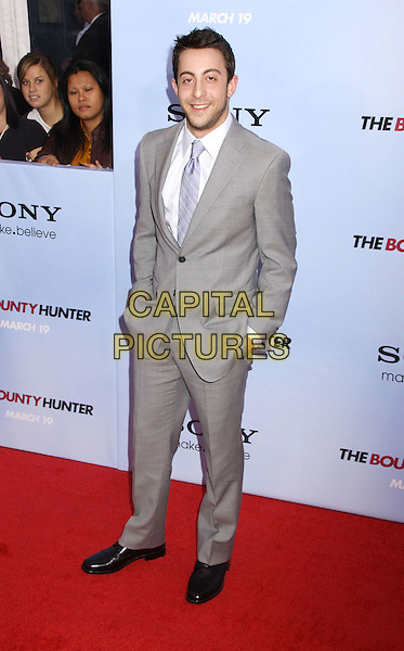 ADAM ROSE.'The Bounty Hunter' New York Premiere held at the Ziegfeld Theatre, New York , NY, USA, 16th March 2010..arrivals full length grey gray suit tie hands in pockets .CAP/ADM/AC.©Alex Cole/AdMedia/Capital Pictures.