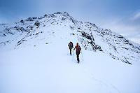 Two hikers in winter hiking towards Hustind mountain peak, Flakstadøy, Lofoten Islands, Norway