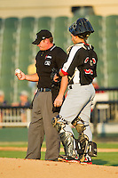 Home plate umpire Jake Wilburn inspects the baseball as he and Hickory Crawdads catcher David Lyon (36) wait for a new pitcher to enter the game against the Kannapolis Intimidators at CMC-Northeast Stadium on July 26, 2013 in Kannapolis, North Carolina.  The Intimidators defeated the Crawdads 2-1.  (Brian Westerholt/Four Seam Images)