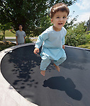 Sanaullah Ahmadzai, 2, bounces on a trampoline as his father, Ahmadullah Ahmadzai, watches in the yard of their home in Harrisonburg, Virginia. Refugees from Afghanistan, they were resettled in Harrisonburg by Church World Service.<br /> <br /> Photo by Paul Jeffrey for Church World Service.