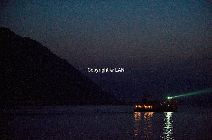 Evening landscape view of a commercial river freighter with a spotlight on the Cháng Jiāng near the Wànzhōu District in the Chongqing Municipality.  © LAN