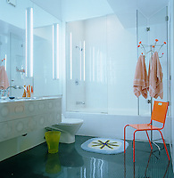 The floors and cupboards in this otherwise stark white bathroom are covered in a computer-generated 'digi-pop' print