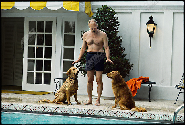 US President Gerald Ford with his golden retrievers, Liberty and Misty, at the White House swimming pool. Washington DC, USA, May 1976