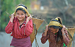 Young women carry heavy loads in Dhawa, a village in the Gorkha District of Nepal.