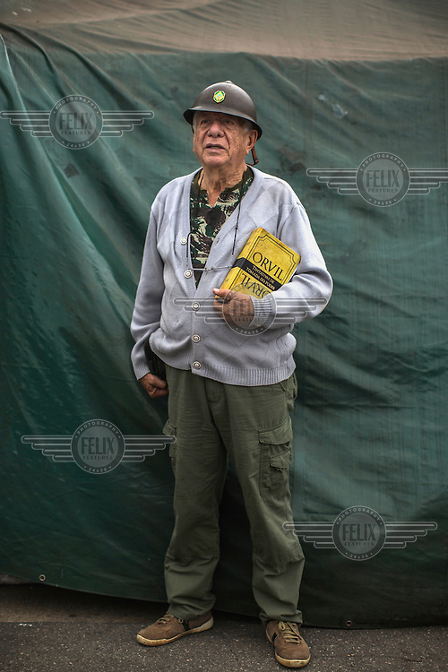 Retired sheriff Alberto Augusto, 72, of the Brazilian Interventionist Resistence Movement (MBRI), who is wearing his grandfather's helmet from 1932, at their headquarters, called PR 1 - Sergeant Mario Kozel Filho Military Interventionist Camp, a radical group that wants military intervention of the government.<br /> <br /> Their headquarters is a makeshift tarpaulin camp situated on an island in the middle of Sergeant Mario Kozel Filho Avenue, between the State Legislative Assembly and the Ministry of the Military. <br /> <br /> Augusto holds a book, called Orvil (which is book spelled backwards in Portuguese ). After the end of the military dictatorship (1 April, 1964 to 15 March, 1985), a military commission produced a report on the events that occurred between 1964 and 1985 during the military's armed conflict with the left. It was developed in secrecy over three years and completed in 1988.