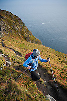 Female hiker hiking mountain trail on Reinebringen, Lofoten islands, Norway