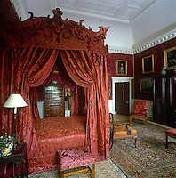Crimson silk brocade envelops the four-poster bed in this grand bedroom