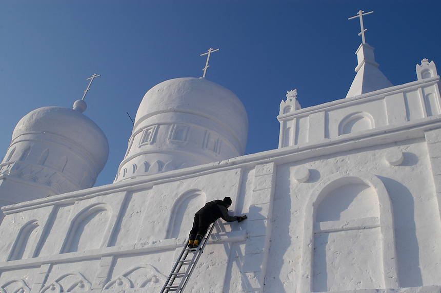 A man carves final building details into a replica church made completely of snow during the 2006 Snow and Ice Festival in Harbin, China on January 4, 2006. The festival features large-scale carvings of snow and ice in several locations throughout the city, with many global monuments recreated in a temporary winter fantasy world.