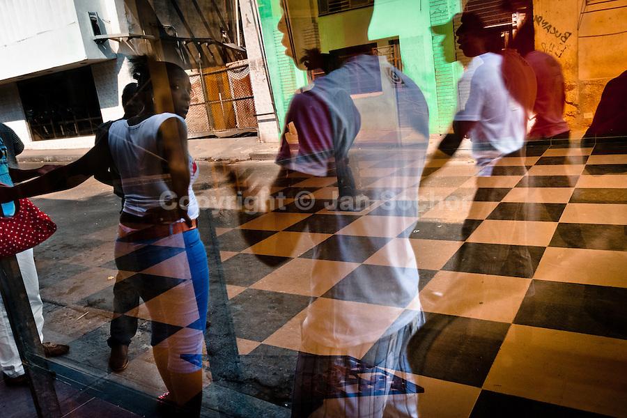 A reflection of Cubans, walking on the street, is seen in a shop window in Havana, Cuba, 15 February 2009.