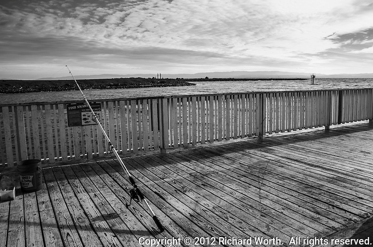 A fishing pole and bait bucket on a fishing pier on a late autumn afternoon.