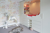 A young girl's pretty bedroom has a raised bed built into a recess. A wardrobe on either side and set in drawers provides plenty of storage.