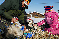 Paul Johnson boots his dogs as Ella Bird Mercer pets one Saturday morning at the Shageluk checkpoint during Iditarod 2011..