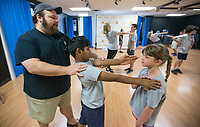 NWA Democrat-Gazette/BEN GOFF @NWABENGOFF<br /> Chris Tennison (from left), head of academy, helps Vish Vikram, 7, of Bentonville and Cecilia Teague, 8, of Rogers learn stage combat technique Tuesday, June 11, 2019, during the Shakespeare Camp at Trike Theatre in Bentonville. The five-day camp is one of many offered by Trike Theatre over the summer. Trike Theatre is also presenting the Northwest Arkansas Shakespeare Festival this week with performances of 'A Midsummer Night's Dream' at 7:00 p.m. Thursday, Friday and Saturday at Train Station Park across from the Bentonville Public Library.