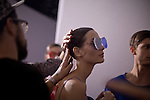 A model gets her hair touched up before going on the runway for the Brazilian brand, Osklen, at São Paulo Fashion Week for Summer Season 2013/2014, at Bienal, in Ibirapuera Park, São Paulo, Brazil, on Thursday, March 21, 2013.