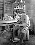 Jerome ID:  Brady Stewart peeling potatos in his farm house - 1909.  A Calendar and food products in the background.   Brady Stewart and three friends went to Idaho on a lark from 1909 thru early 1912. As part of the Mondell Homestead Act, they received a land grant of 160 acres north of the Snake River.  For 2 ½  years, Brady Stewart photographed the adventures of farming along with the spectacular landscapes.