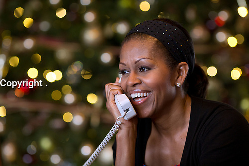 First Lady Michelle Obama reacts while talking on the phone to children across the country as part of the annual NORAD Tracks Santa program. Mrs. Obama answered the phone calls from Kailua, Hawaii, Christmas Eve, Dec. 24, 2012.<br /> (Official White House Photo by Pete Souza)