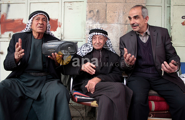 Palestinian men listen to the radio in the West Bank city of Hebron on May 04, 2011 as Palestinians in the West Bank and Gaza Strip gather to celebrate and welcome a reconciliation deal signed by rival movements Hamas and Fatah in Cairo. Photo by Najeh Hashlamoun