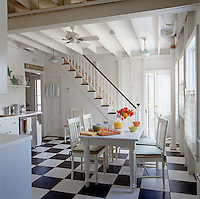 A pottery barn table is the heart of the white washed kitchen.