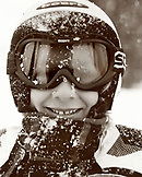 USA, Utah. boy wearing ski goggles with a face full of snow, Alta Ski Resort (B&W)