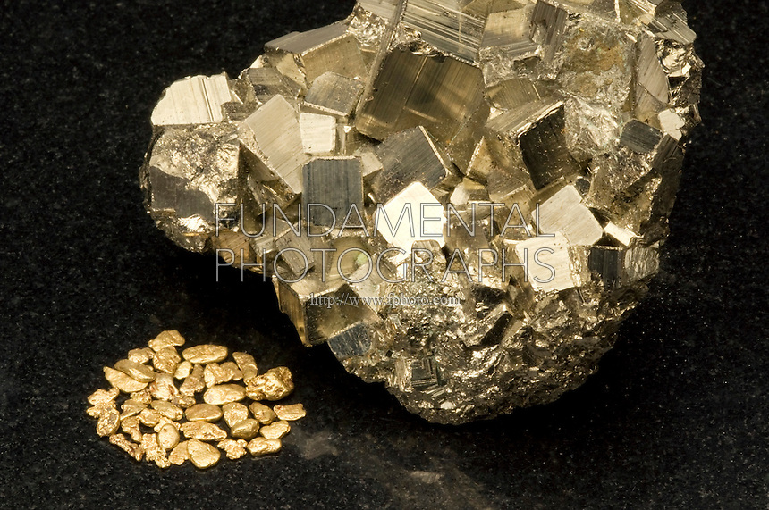 "IRON PYRITE AND GOLD COMPARISON<br /> (Variations Available)<br /> Gold nuggets compared to ""Fool's Gold""<br /> The mineral iron pyrite has a simple cubic structure. It is also known as iron sulfide (FeS2) or Fool's Gold because of its similar lustre to gold. Gold (Au) is a malleable and ductile transition metal. Pyrite is sometimes found in association with gold."