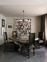 In the dining area, a Soane table base is topped with Portoro marble, the candlesticks belonged to Kim Hersov's grandmother anf the leather chairs are Spanish. The painting is by Barry Reigate and the Italian chandelier is from the 1960s