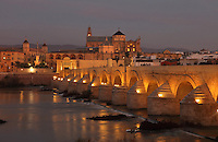 The Roman bridge in the evening, built 1st century BC over the Guadalquivir river, and behind, the Cathedral-Great Mosque of Cordoba, in Cordoba, Andalusia, Southern Spain. The first church built here by the Visigoths in the 7th century was split in half by the Moors, becoming half church, half mosque. In 784, the Great Mosque of Cordoba was built in its place, but in 1236 it was converted into a catholic church, with a Renaissance cathedral nave built in the 16th century. The historic centre of Cordoba is listed as a UNESCO World Heritage Site. Picture by Manuel Cohen