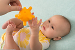 4 month old baby girl on back reaching for dangled toy with both hands