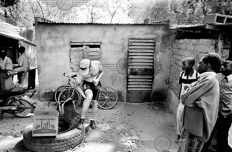 ©Chris Keulen/Panos Pictures..Burkina Faso, Sabou, 17/11/2000.Dutch cyclist Wout Conijn oiling his legs before start of 3th course in Tour du Faso while locals watching him.