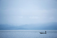 A fisherman in a dugout canoe in the early morning off the coast of island reserve Nosy Mangabe, Madagascar