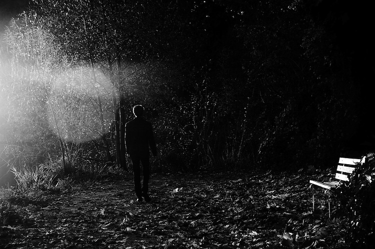 A man walking through the woods as mystical and magical light enters the frame from the left, outlining him in a thin ribbon of light. A bed of of fallen autumn leaves along the ground.