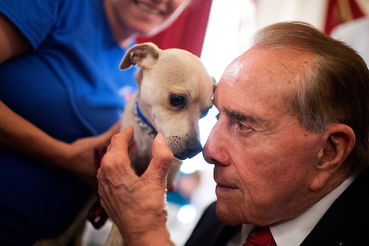 """UNITED STATES - JULY 30: Former Sen. Bob Dole, R-Kan., pets """"Eddie"""" during the ASPCA's Fourth Annual Paws for Celebration pet adoption event in Cannon Building, July 30, 2015. (Photo By Tom Williams/CQ Roll Call)"""