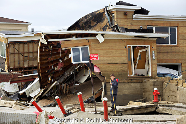 BELLE HARBOR, NEW YORK-NOVEMBER 01: A young boy stands in front of a destroyed home on the beach in this Rockaway, Queens neighborhood after Hurricane Sandy November 1, 2012. A large number of homes and businesses were destroyed by the storm and much of the area is without power.