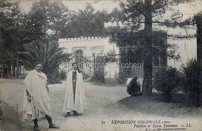 Tunisia Pavilion and Tunisian men in traditional dress at the Colonial Exhibition of 1907, held in the Jardin d'Agronomie Tropicale, or Garden of Tropical Agronomy, in the Bois de Vincennes in the 12th arrondissement of Paris, postcard from the nearby Musee de Nogent sur Marne, France. The garden was first established in 1899 to conduct agronomical experiments on plants of French colonies. In 1907 it was the site of the Colonial Exhibition and many pavilions were built or relocated here. The garden has since become neglected and many structures overgrown, damaged or destroyed, with most of the tropical vegetation disappeared. The site is listed as a historic monument. Picture by Manuel Cohen / Musee de Nogent sur Marne
