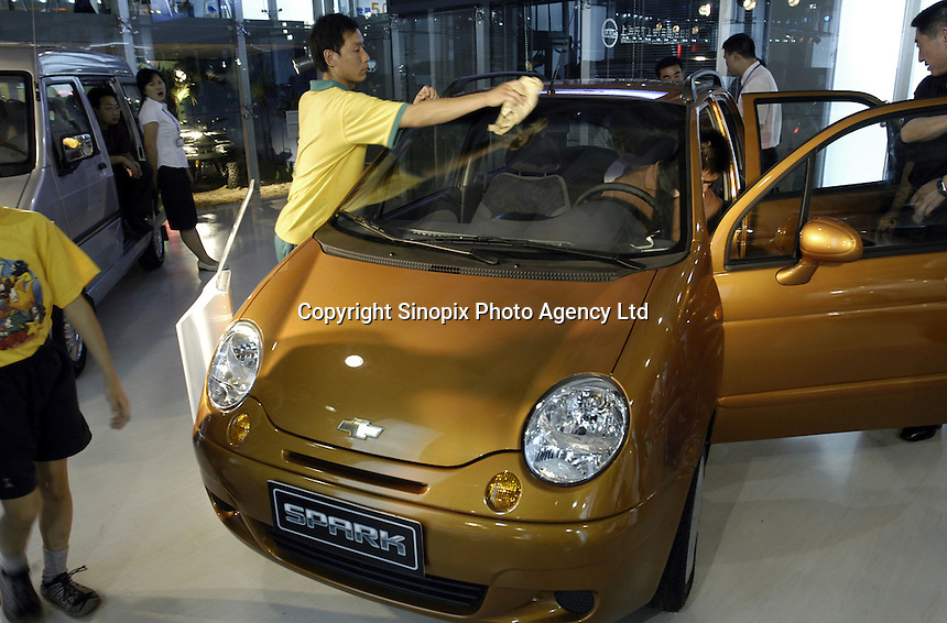 A cleaner wipes a  Chevrolet Spark, a mini-car by GM's SAIC-GM-Wuling at the Auto China 2004 exhibition in Beijing, China. General Motors had partnered up with the Shanghai Automotive Industry Corporation in 1997 to establish the Shanghai General Motors joint venture..