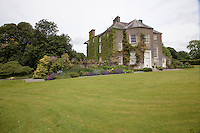 A sweeping lawn bordered by well-stocked flowerbeds slopes away from Burtown House