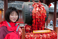 Nanjing, Jiangsu, China.  Young Woman in the Drum Pavilion of the Confucian Temple Complex.  Red tassles and tags are prayers for good luck.