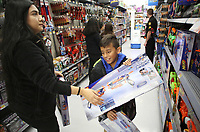 NWA Democrat-Gazette/DAVID GOTTSCHALK Jessica Torres, report specialist with the Springdale Police Department, shops Tuesday, December 4, 2018, with Jeffrey Mira, 10, at the Walmart Supercenter on Pleasant Street in Springdale. More than 200 children participated in the Springdale Police Department Shop with a Cop program. The department collected $45,000 this year for the program.