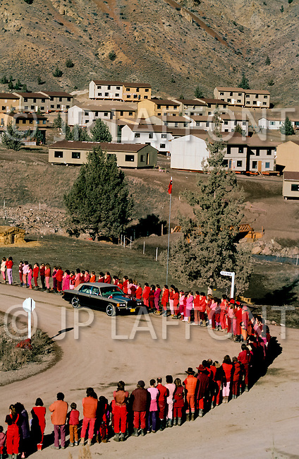 Wasco, Oregon, January 1984: Disciples of Bhagwan Rajneesh, wait in line along the roads of Rajneeshpuram to greet him during  his daily trip through the community in his Rolls-Roys. Bhawan Rajneesh (now known as Osho) possessed more than 20 Rolls-Royce cars and never used the same car two days in a row. Rajneeshpuram, was an intentional community in Wasco County, Oregon, briefly incorporated as a city in the 1980s, which was populated with followers of the spiritual teacher Osho, then known as Bhagwan Shree Rajneesh. The community was developed by turning a ranch from an empty rural property into a city complete with typical urban infrastructure, with population of about 7000 followers.