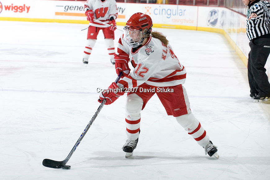 MADISON, WI - FEBRUARY 16: Heidi Kletzien #12 of the Wisconsin Badgers women's hockey team handles the puck against the Bemidji State Beavers at the Kohl Center on February 16, 2007 in Madison, Wisconsin. The Badgers beat the Beavers 2-0. (Photo by David Stluka)