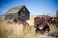 Long-ago abandoned antique cars and tractors stand in a field next to a homestead on the Coffee Ranch in Rosebud County near Melstone and Sumatra, Montana, USA.