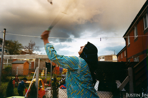 A Muslim woman, whose family came from Malawi, plays badminton in her lawn in Leicester city. ..Leicester is expected to be the first city in the UK to have a majority non-white population within the next few years. It is one of the most ethnically-diverse cities in Europe. ....Picture taken April 2005 by Justin Jin
