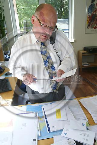 BRUSSELS - BELGIUM - 21 JUNE 2004--Hans BENDER, Danish Dairy Board (Mejeriforeningen) Brussels EU Office, opening letters while speaking in telephone.-- PHOTO: ERIK LUNTANG / EUP-IMAGES